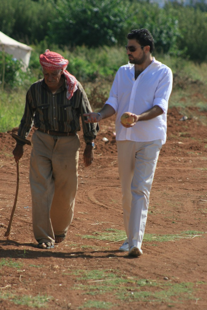 Julie's cousin walking alongside a Syrian farmer in his olive groves.